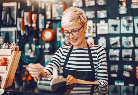 Myyjä tarkastelee maksupäätteen kuittia varaosaliikkeessä