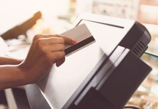 Myyjä napauttaa kassan näyttöä maksukortin kulmalla
