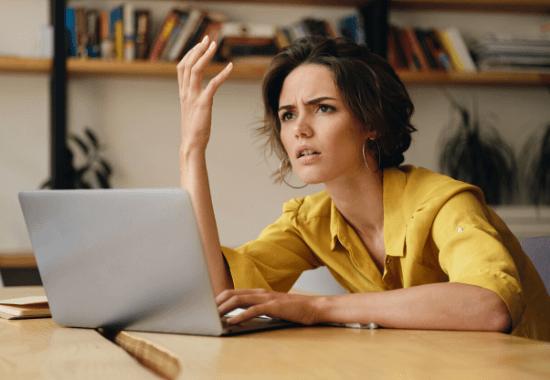 Nainen ihmettelee harmissaan tietokoneen äärellä