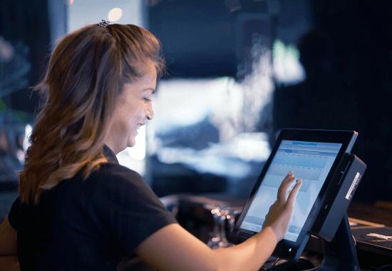 Nainen naputtaa kassajärjestelmää sormella